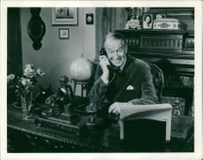 Maurice Chevalier talking on phone and smiling.