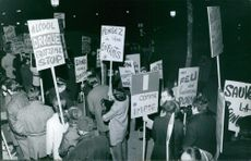 People on a rally carrying placards.