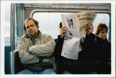 Subway users read the newspaper.