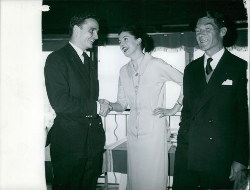A woman pictured shaking hands with the man on her right, while the Major Camille Rayon (left) stands still and smiled.