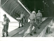 Uniformed men carrying boxes from the plane.