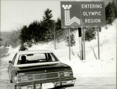 A car drives past the sign at the entrance to Lake Placid during the 1980 Winter Olympics