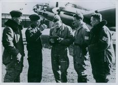 Air forces officers standing together in airfield and discussing, 1939.
