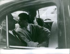Men siting in the car and looking back.