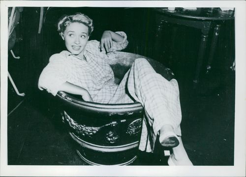 Jane Powell candidly sits inside a large vase.