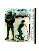 A young bosnian girl cycles past french soldier.