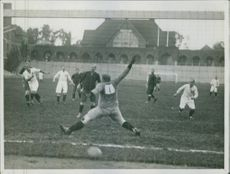 People playing football in ground.