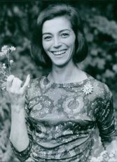 Marisa Pavan smiling, facing camera holding flowers.
