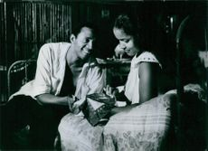 Marpessa Dawn sitting on bed with a man.  French Selection at 1959 Cannes Film Festival