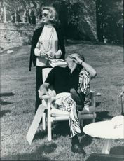 Kirk Douglas with Anne Buydens relaxing outdoor.