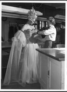 Gunilla Bentele, get help at NK's French department with the final of her costume - a sparkly pink tulle dream, designed by Gota Tragardh.