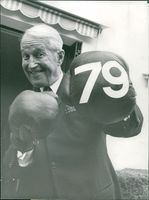 Maurice Auguste Chevalier showing boxing moves on his 79th birthday.