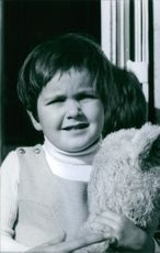 1971 Portrait of a child, holding toy.