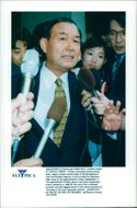 Koko Sato surrounded by reporters