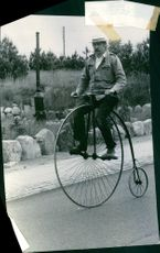 A man riding a Penny-farthing bicycle.