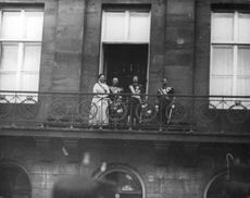 Royal people standing on balcony.
