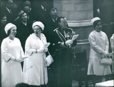 Beatrix and Juliana of the Netherlands standing in a church singing.