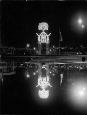 An illuminated giant crown is reflecting in the water.