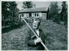 Willy Brandt in a garden, holding a spade in hands and looking at something.