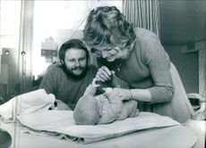 A scene of singer duo from Mouscron, Belgium Serge & Christine Ghisolan  looking their baby and smiling. 1970