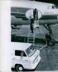 Men holding cage getting off from airplane.