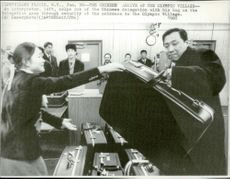 China's athletes go through security checks on their arrival to the Olympic Village in front of the 1980 Winter Olympics