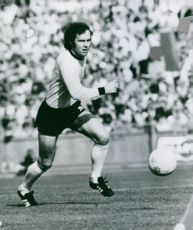 Franz Anton Beckenbauer running  after the ball during the football match.