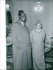 Modibo Keita is standing in a hallway with King Mohammed of Morocco during a conference in Casablanca.