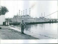 A man standing on a harbor. 1970