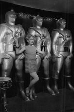 Carroll Baker posing in front of sculptures.