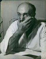 A photo of a patient sitting on a hospital bed covering his mouth. 1948