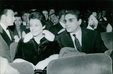 Robert Hossein sitting with woman and looking at something.