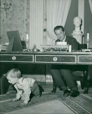 A man in his office desk with a child crawling underneath.