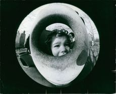 A young girl staring from the hole.