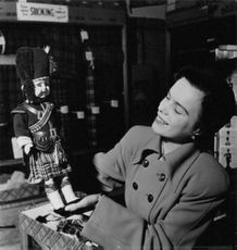 Woman holding a man doll wearing Royal Regiment Scottish kilt uniform.