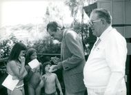 Richard Nixon signs autographs during the charity golf round at LaCosta Country Club. In the foreground is Frank E. Fitzsimmons.