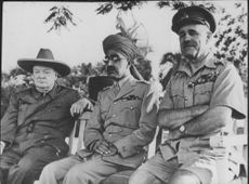Sir Winston Leonard Spencer-Churchill sitting with two Police Officer.