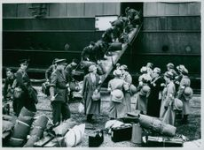 Members of the Q.A.I.M.N.S. on the quayside at Cherbourg having disembarked from the Biarritz. R.A.F. men are unloading their baggage from the troopship.