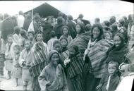 Poor women and children gathered in front of a camp.