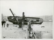 People standing near the damaged ship due to the explosion.
