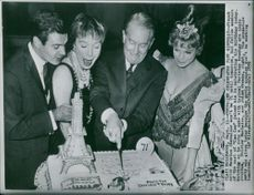 Maurice Chevalier cutting a cake designed of paris.