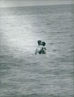 Sylvia Casablancas embracing man in the sea.