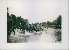 Soldiers crossing a stream riding a horse during the first world war.