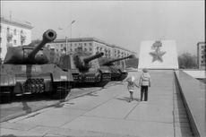 Two young children in Volgograd pass the armored troops that helped turn the Second World War
