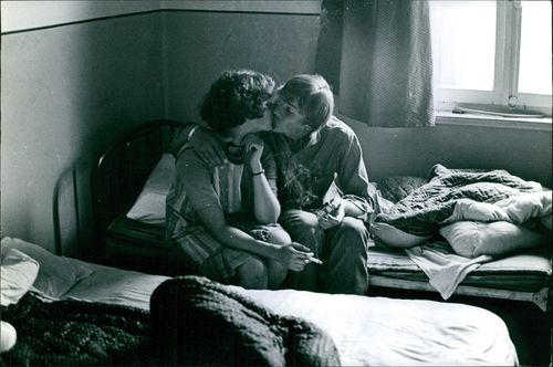 A couple pictured sitting on a bed and kissing each other on the lips.