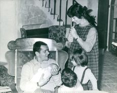 Serge Reggiani sitting and smiling while holding a baby with his wife and two children, 1963.