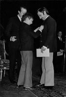 Philippe of Belgium has assisted by his father, Albert II of Belgium to put a something on man's suit.