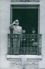 1964 A photo of people standing inside a building...the man beside the old man and a woman performing salute maybe somebody is arriving that they need to give an honor.