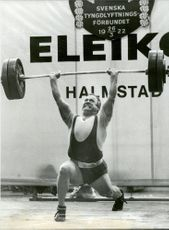 Ingvar Asp in knee position while lifting heavily in front of spectators in an unknown context