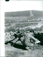 A soldier sitting besides cannon.